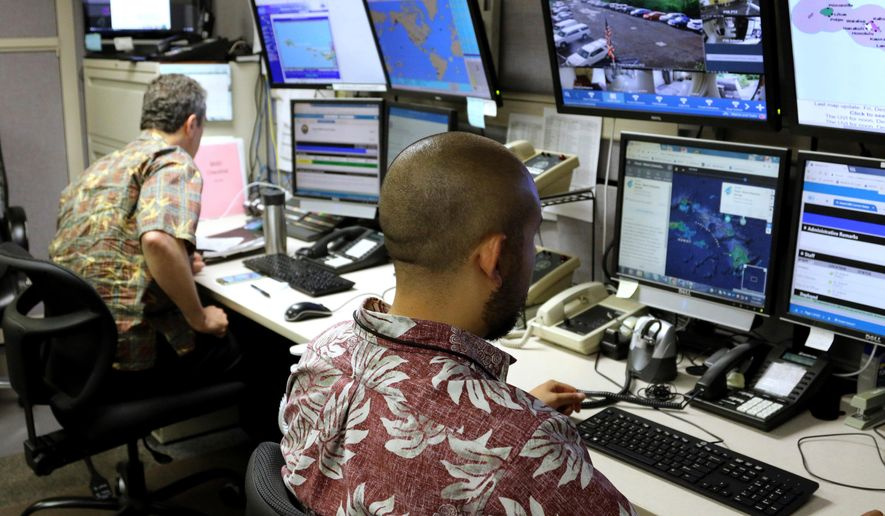 FILE - In this Dec. 1, 2017 file photo, Hawaii Emergency Management Agency officials work at the department's command center in Honolulu. U.S. Sen. Brian Schatz of Hawaii is holding a hearing on how and why the state of Hawaii in January mistakenly sent alerts warning that a ballistic missile was about to hit the islands. The Thursday, April 5, 2018 hearing in Honolulu is also expected to address options for improving emergency alerts. Schatz, a Democrat and ranking member of the Senate Subcommittee on Communications, Technology, Innovation and the Internet, has introduced legislation to give the federal government sole responsibility for handling missile alerts. (AP Photo/Caleb Jones, File)