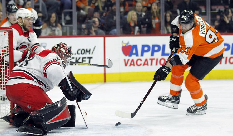 Philadelphia Flyers' Jakub Voracek, right, attacks as Carolina Hurricanes goalie Scott Darling defends during the second period of an NHL hockey game Thursday, April 5, 2018, in Philadelphia, Pa. (AP Photo/Tom Mihalek)
