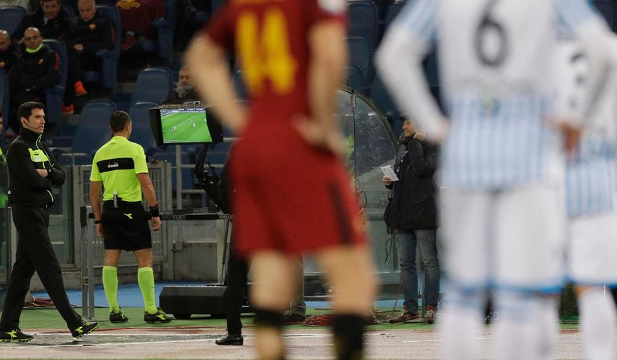 FILE -- In this Dec. 1st, 2017 file photo, referee Rosario Abisso, second from left, checks the Video Assistant Referee (VAR) during an Italian Serie A soccer match between AS Roma and Spal, at the Olympic stadium in Rome. The Italian referees association says it has been sent packages filled with bullets. The development comes amid fan protests over the video assistant referee (VAR), which is being introduced in Serie A this season to mixed results. (AP Photo/Gregorio Borgia)
