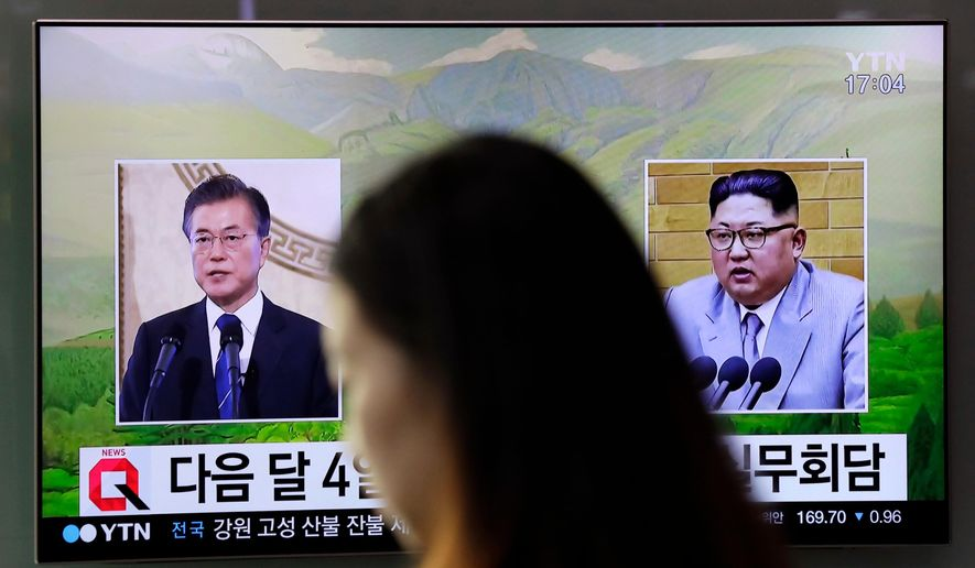 FILE - In this March 29, 2018, file photo, a visitor walks by a TV screen showing file footages of South Korean President Moon Jae-in, left, and North Korean leader Kim Jong Un, right, during a news program at the Seoul Railway Station in Seoul, South Korea. The rival Koreas started on Thursday, April 5, 2018, preparatory talks to set up a summit later this month between North Korean leader Kim Jong Un and South Korean President Moon Jae-in amid a global diplomatic push to resolve tensions over the North's nuclear program. (AP Photo/Lee Jin-man. File)