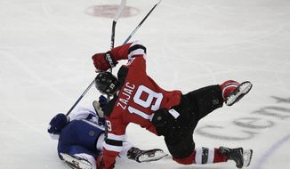 Toronto Maple Leafs center Auston Matthews, left, and New Jersey Devils center Travis Zajac get tangled up during the third period of an NHL hockey game, Thursday, April 5, 2018, in Newark, N.J. (AP Photo/Julio Cortez)