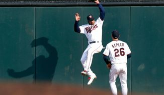 Minnesota Twins' Byron Buxton, left, pulls in a long fly ball off the bat of Seattle Mariners' Mitch Haniger during the fifth inning of a baseball game Thursday, April 5, 2018, in Minneapolis. Looking on is right fielder Max Kepler. (AP Photo/Jim Mone)