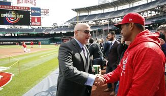 Washington Nationals general manager Mike Rizzo, left, shakes hands with manager Dave Martinez on the field before the home opener baseball game against the New York Mets at Nationals Park, Thursday, April 5, 2018, in Washington. (AP Photo/Alex Brandon) **FILE**