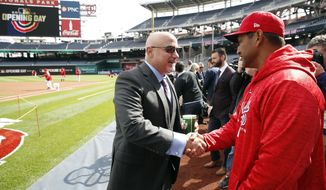 Washington Nationals general manager Mike Rizzo, left, shakes hands with manager Dave Martinez on the field before the home opener baseball game against the New York Mets at Nationals Park, Thursday, April 5, 2018, in Washington. (AP Photo/Alex Brandon)