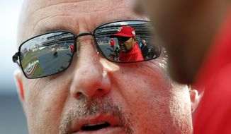 Washington Nationals general manager Mike Rizzo speaks with manager Dave Martinez, seen in Rizzo's sunglasses, before the home opener baseball game against the New York Mets at Nationals Park, Thursday, April 5, 2018, in Washington. (AP Photo/Alex Brandon) **FILE**