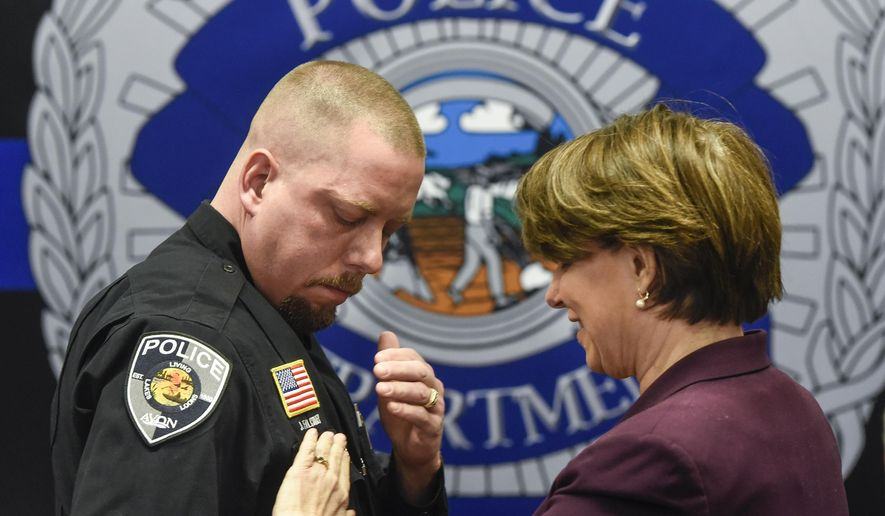U.S. Sen. Amy Klobuchar presents officer Jason Falconer with the Congressional Badge of Bravery Award during a ceremony Thursday, April 5, 2018, at the St. Cloud Police Department in St. Cloud, Minn. (Dave Schwarz/The St. Cloud Times via AP)