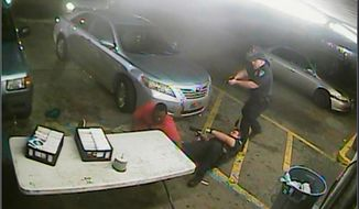 FILE - In this still, file image taken from security camera video provided Friday, March 30, 2018, by the Baton Rouge Police Department, officers Blane Salamoni and Howie Lake II confront Alton Sterling, left, during a struggle outside the Triple S Food Mart in Baton Rouge, La., in July 2016. Lake returned to work Thursday, April 5, for the first time since his partner's fatal shooting of Sterling, a 37-year-old black man whose death was caught on video and set off widespread protests nearly two years ago. (Courtesy of Baton Rouge Police Department via AP)