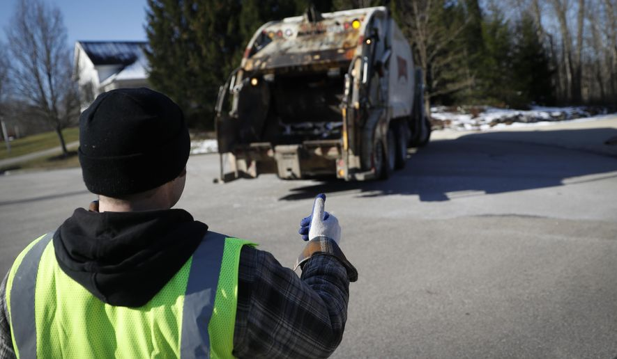 In this March 23, 2018, photo, trainee Brent Cottongin, with Rumpke Waste & Recycling, directs his garbage truck driver as he works a residential route in Beavercreek, Ohio.  (AP Photo/John Minchillo) **FILE**
