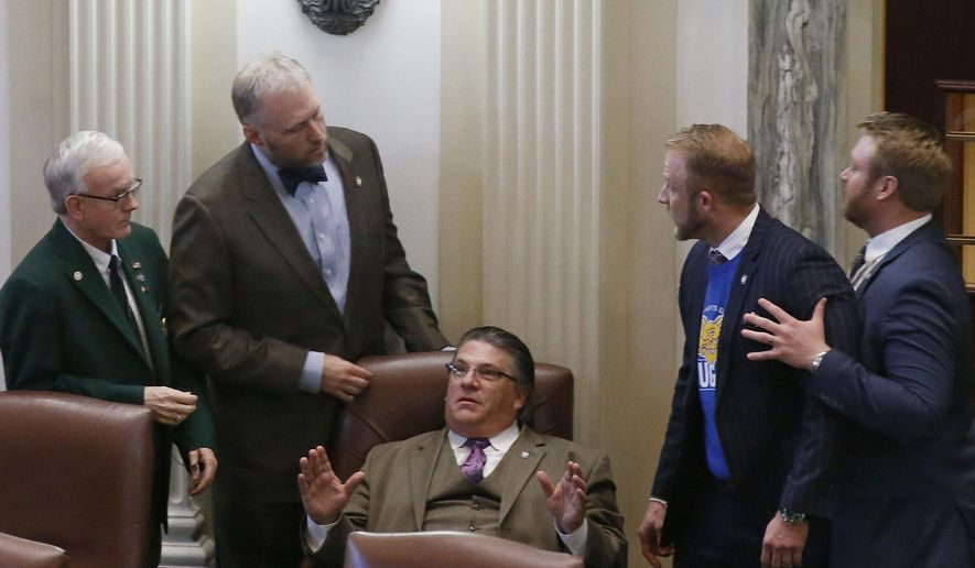 Oklahoma state Rep. Chad Caldwell, second from left, R-Enid, and Rep. Colin Walke, second from right, D-Oklahoma City, exchange words on the House floor during a discussion of a funding bill in Oklahoma City, Wednesday, April 4, 2018, as supporters of school funding fill the gallery. (AP Photo/Sue Ogrocki)
