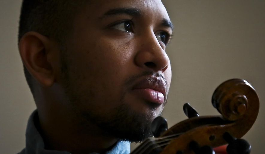 In this March 28, 2018 video still, Venezuelan musician Wuilly Arteaga holds his violin during an interview, in New York. The young violinist gained fame after playing somber renditions of Venezuela's national anthem during the 2017 protests. (AP Photo/Bebeto Matthews)