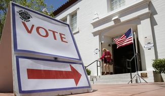 FILE - In this June 14, 2016, file photo, a woman walks out of a polling place after voting in the Nevada primary election in Las Vegas. Nevada's top election official, Secretary of State Barbara Cegavske, says more than 63,000 names were removed from statewide voter registration rolls last month. (AP Photo/John Locher, file) **FILE**