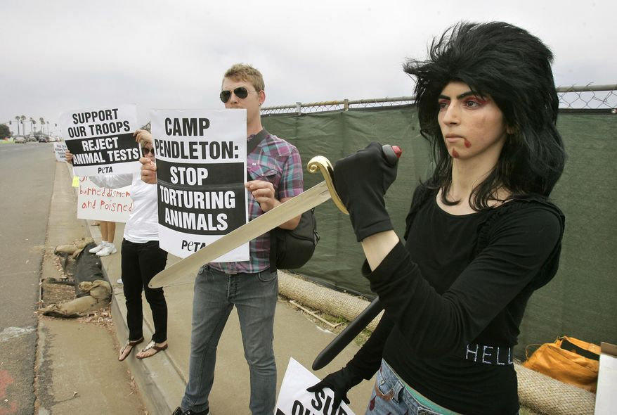 Nasim Aghdam, right, poses with members of People for the Ethical for Animals, PETA, as the protested at the main gate of Marine Corps base Camp Pendleton in Oceanside, California, Aug. 12, 2009. (Charlie Neuman/The San Diego Union-Tribune via AP)