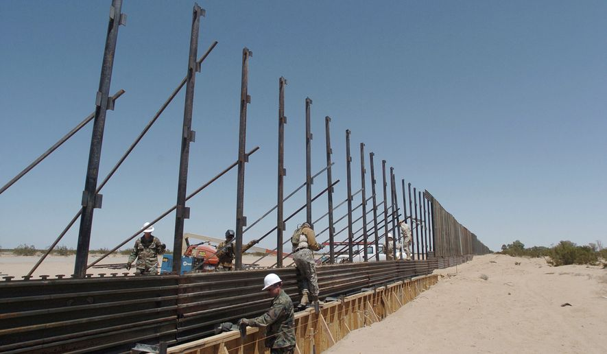 FILE - In this June 8, 2006, file photo, members of the National Guard work on construction of a border wall at the U.S.-Mexico border next to San Luis Rio Colorado, Mexico. Photo was taken from a few steps into the United States. The arrival of U.S. National Guard troops in Arizona has scared off illegal Mexican migrants along the border as a whole, significantly reducing crossings, according to U.S. and Mexican officials. From 2006 to 2008, the Guard fixed vehicles, maintained roads, repaired fences and performed ground surveillance. (AP Photo/David Maung, File)