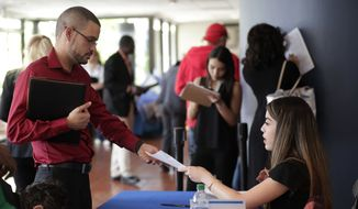 In this Jan. 30, 2018, file photo, an employee of Aldi, right, takes an application from a job applicant at a JobNewsUSA job fair in Miami Lakes, Fla. On Friday, April 6, 2018, the U.S. government issues the March jobs report. (AP Photo/Lynne Sladky, File)
