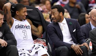 Washington Wizards guard John Wall, right, talks with guard Bradley Beal on the bench during the second half of the team's NBA basketball game against the Atlanta Hawks, Friday, April 6, 2018, in Washington. The Hawks won 103-97. (AP Photo/Nick Wass)