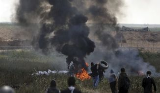 Palestinian protesters burn tires during a protest at the Gaza Strip's border with Israel, Friday, April 6, 2018. (AP Photo/ Khalil Hamra)