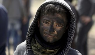 A Palestinian boy poses for a photograph as he paints his face in black during a protest at the Gaza Strip's border with Israel, Friday, April 6, 2018. (AP Photo/ Khalil Hamra)