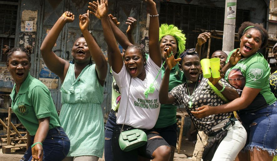Supporters of opposition presidential candidate Julius Maada Bio celebrate his election victory in Freetown, Sierra Leone, Thursday, April 5, 2018. Sierra Leone's former ruling party intends to challenge the results of the presidential runoff vote in court, the losing candidate announced after the opposition party won for the first time in a decade. (AP Photo/Cooper Inveen)