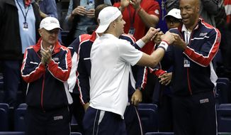 John Isner, of the United States, celebrates with his team after defeating Joris De Loore, of Belgium, in a Davis Cup quarterfinal singles tennis match Friday, April 6, 2018, in Nashville, Tenn. (AP Photo/Mark Humphrey)