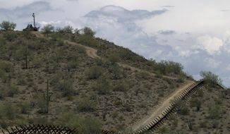 FILE - In this July 29, 2010, file photo, a U.S. National Guard vehicle guards covered under camouflage fabric sits atop a mountain next to the border fence near Sonoyta, Mexico. The U.S. National Guard faces a vastly different landscape than it did on its last two deployments to the Mexican border but its role is shaping up much the same: moving Border Patrol agents from behind-the-scenes jobs to making arrests on the front lines. Arrests had fallen by about half and hundreds of miles of border barriers were added by May 2010, when Operation Phalanx sent 1,200 troops to the border amid backlash to the killing of an Arizona rancher. Crossers were still largely Mexican men entering the country through Arizona deserts. (AP Photo/Guillermo Arias)