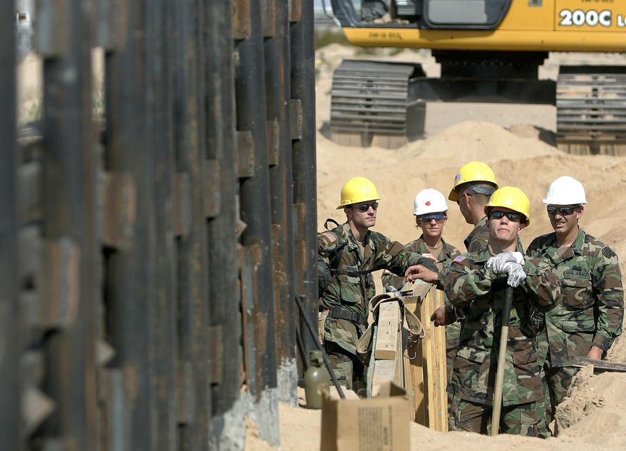 FILE - In this Monday, June 5, 2006, file photo, Utah National Guard troops from the 116th Construction Equipment Support Company, the first National Guard unit along the border as part of Operation Jump Start, prepare to extend a wall along the U.S.-Mexico border in San Luis, Ariz. In 2018, the U.S. National Guard faces a vastly different environment than it did on its last two deployments to the border with Mexico, with far fewer illegal crossings and more Central Americans than Mexicans coming. (AP Photo/Khampha Bouaphanh, File)