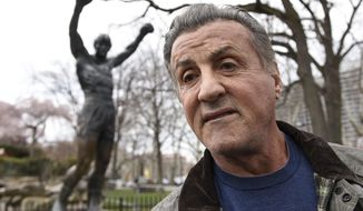 "Sylvester Stallone talks to reports in front of the Rocky statue for a ""Creed II"" photo op, Friday, April 6, 2018, in Philadelphia. The film, part of the ""Rocky"" film franchise, will be released later this year. (AP Photo/Michael Perez)"