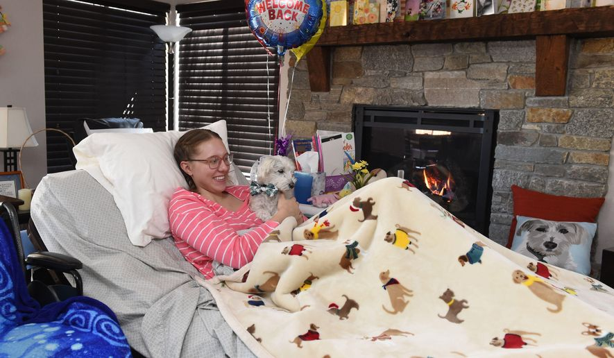 Annika Kerns lies with her dog Buster on the hospital bed that her parents have set up in the living room of their Reno, Nevada, home Wednesday, April 4, 2018. Nearly a month ago, Annika, 18, was hit by a train as she hiked past a no-trespassing sign with her boyfriend, a friend and her dog Buster. (Andy Barron/The Reno Gazette-Journal via AP)