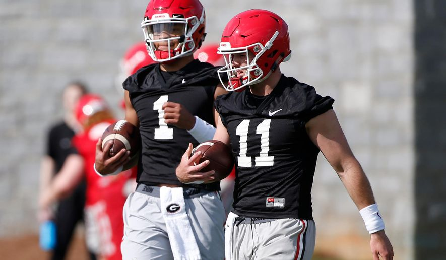 FILE - In this March 20, 2018, file photo, Georgia quarterbacks Justin Fields (1) and Jake Fromm (11) look on during the opening day of spring NCAA college football practice, in Athens, Ga. (Joshua L. Jones/Athens Banner-Herald via AP, File)/Athens Banner-Herald via AP)
