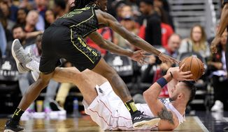 Atlanta Hawks forward Taurean Prince, top, vies for the ball against Washington Wizards center Marcin Gortat, of Poland, during the second half of an NBA basketball game Friday, April 6, 2018, in Washington. The Hawks won 103-97. (AP Photo/Nick Wass)