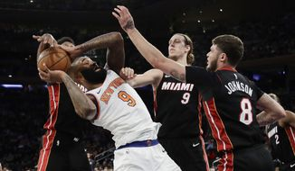 New York Knicks' Kyle O'Quinn (9) is defended by Miami Heat's Tyler Johnson (8), Kelly Olynyk (9), and James Johnson during the second half of an NBA basketball game Friday, April 6, 2018, in New York. The Knicks won 122-98. (AP Photo/Frank Franklin II)