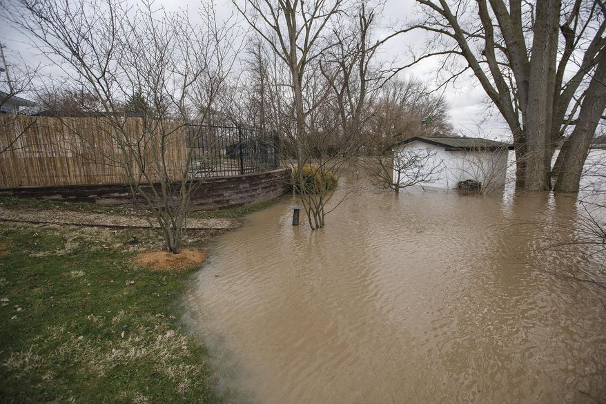 Floodwaters from the Flatrock River have reached the back yards of homes in the Lagoons neighborhood in Columbus, Ind., Wednesday, April 4, 2018. Several central and southern Indiana schools were closed Wednesday or on two-hour delays due to local street flooding.(Mike Wolanin/The Republic via AP)