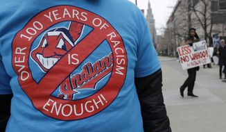 A man wears a shirt in protest of Chief Wahoo before a home opener baseball game between the Kansas City Royals and the Cleveland Indians, Friday, April 6, 2018, in Cleveland. (AP Photo/Tony Dejak)
