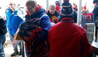 A Minnesota Twins fan enters the stadium with blankets in mid-30's temperatures prior to the Twins home opener baseball game Thursday, April 5, 2018, in Minneapolis. (AP Photo/Jim Mone)