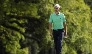 Haotong Li, of China, walks to the 18th green during the first round at the Masters golf tournament Thursday, April 5, 2018, in Augusta, Ga. (AP Photo/Chris Carlson)