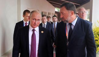 File-This Nov. 10, 2017, file photo shows Russia's President Vladimir Putin, left, and Russian metals magnate Oleg Deripaska, right, walking to attend the APEC Business Advisory Council dialogue in Danang, Vietnam. The United States punished dozens of Russian oligarchs and government officials on Friday, April 6, 2018, with sanctions that took direct aim at President Putin's inner circle, as President Donald Trump's administration tried to show he's not afraid to take tough action against Moscow. Seven Russian tycoons, including aluminum magnate Deripaska, were targeted, along with 17 officials and a dozen Russian companies, the Treasury Department said.  (Mikhail Klimentyev, Sputnik, Kremlin Pool Photo via AP, File) **FILE**