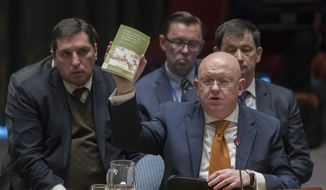"Russian Ambassador to the United Nations Vassily Nebenzia holds up a copy of ""Alice's Adventures in Wonderland"" as he speaks during a Security Council meeting on the situation between Britain and Russia Thursday, April 5, 2018, at United Nations headquarters. (AP Photo/Mary Altaffer)"