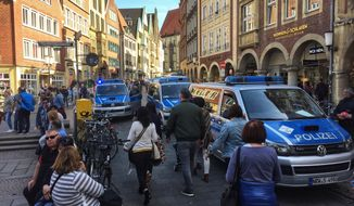 Police vans stand in downtown Muenster, Germany, Saturday, April 7, 2018. German news agency dpa says several people killed after car crashes into crowd in city of Muenster.  (dpa via AP)