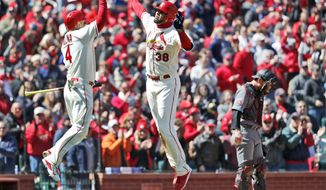 St. Louis Cardinals' Jose Martinez (38) is congratulated by teammate Yadier Molina (4) after hitting a three-run home run as Arizona Diamondbacks catcher Jeff Mathis, right, stands by during the third inning of a baseball game Saturday, April 7, 2018, in St. Louis. (AP Photo/Jeff Roberson)