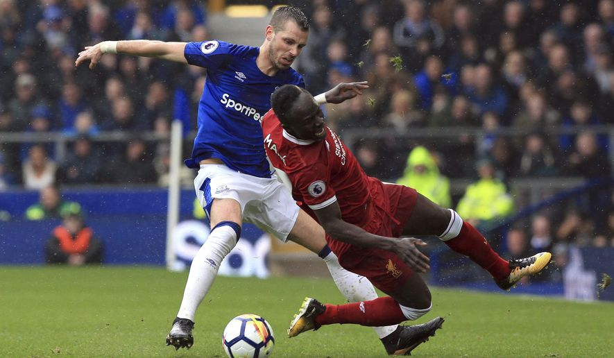 Everton's Morgan Schneiderlin, left, and Liverpool's Sadio Mane during their English Premier League soccer match at Goodison Park in Liverpool, England, Saturday April 7, 2018. (Peter Byrne/PA via AP)