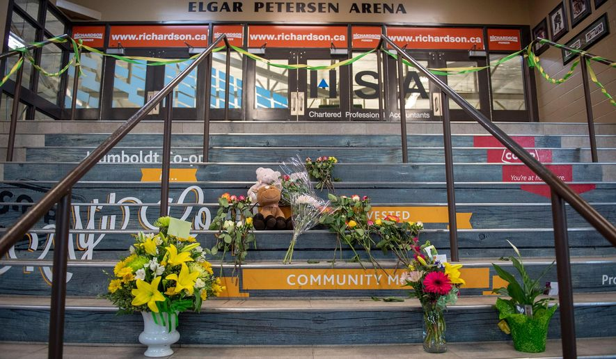 A memorial of flowers and cards sits on the stairs leading into Elgar Petersen Arena, home of the Humboldt Broncos hockey team, in Humboldt, Saskatchewan, on Saturday, April 7, 2018. Canadian police said early Saturday, April 7, 2018,  that several people were killed and others injured after a truck collided with a bus carrying the junior hockey team to a playoff game in Western Canada. Police say there were 28 people, including the driver, on board the bus of the Humboldt Broncos team when the crash occurred around 5 p.m. Friday on Highway 35 in Saskatchewa  (Liam Richards/The Canadian Press via AP)