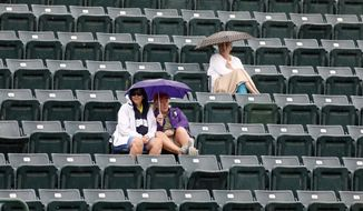 Fans brave the rain during a rain delay in the semifinal match between Anastasija Sevastova, from Latvia, and Julia Goerges, from Germany, at the Volvo Car Open tennis tournament in Charleston, S.C., Saturday, April 7, 2018. (AP Photo/Mic Smith)