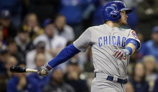 Chicago Cubs' Ian Happ watches his two-RBI single off of Milwaukee Brewers' Jacob Barnes during the ninth inning of a baseball game Saturday, April 7, 2018, in Milwaukee. (AP Photo/Tom Lynn)