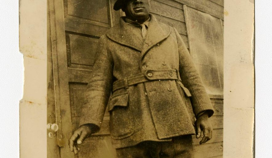 """In a photo provided by the Bentley Historical Library, James """"Big Jim"""" Richardson is photographed outside a cabin in Michigan in 1936. The university has acquired a trove of photos capturing a place and time largely overlooked by history: black Civilian Conservation Corps camps during the Great Depression. The photos are the only known images of the state's segregated, all-black camps. President Franklin Roosevelt established the corps in the early 1930s to employ a """"vast army"""" of unemployed men and restore national resources. (Bentley Historical Library via AP)"""