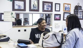 This photo taken March 23, 2018, shows Roslyn Payne greets a customer while working the cash register  at The Four Way Grill, a  soul food restaurant  in Memphis, Tenn. When Irene and Clint Cleaves opened The Four Way Grill in 1946, they couldn't have known that the tiny restaurant attached to a pool hall and a barber shop would become an institution in the civil rights movement 20 years later.  (Brad Vest/The Commercial Appeal via AP)