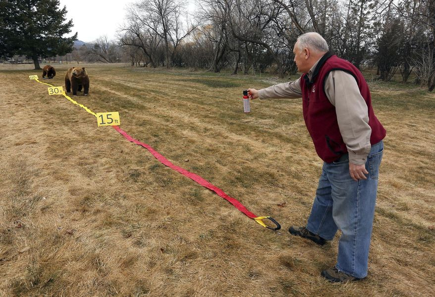 In this March 21, 2018, photo, Be Bear Aware Campaign Director Chuck Bartlebaugh demonstrates how to use bear spray during a training session in Missoula, Mont. Bartlebaugh said if people have time during a grizzly bear attack, they would ideally begin to spray when the bear is still 60 feet away. He suggests aiming slightly downward to create a cloud that meet the bear about 30 feet away. He also recommends using the larger, 7-second can and holding down the trigger until the bear diverts from its charge. (Perry Backus/Ravalli Republic via AP)