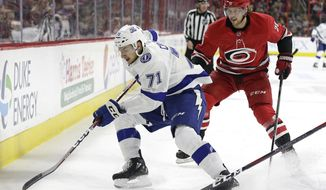 Tampa Bay Lightning's Anthony Cirelli (71) controls the puck while Carolina Hurricanes' Elias Lindholm (28), of Sweden, chases during the first period of an NHL hockey game in Raleigh, N.C., Saturday, April 7, 2018. (AP Photo/Gerry Broome)