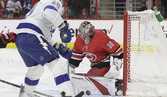 Tampa Bay Lightning's J.T. Miller (10) is blocked by Carolina Hurricanes goalie Cam Ward (30) during the first period of an NHL hockey game in Raleigh, N.C., Saturday, April 7, 2018. (AP Photo/Gerry Broome)