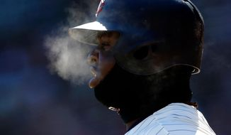 Minnesota Twins' Miguel Sano generates steam as he breathes with the temperatures in the mid-20's while on deck in the first inning of a baseball game against the Seattle Mariners Saturday, April 7, 2018, in Minneapolis. (AP Photo/Jim Mone)