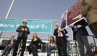 """FILE - In this Feb. 13, 2008, file photo, the late country music legend Merle Haggard, left, is honored with a street named for him Bakersfield, Calif. About 300 people turned out in Bakersfield, California, to celebrate the naming of a post office for Merle Haggard. The late country music legend's sister and widow were among those at a Friday, April 6, 2018, ceremony near downtown honoring Haggard, who helped create the twangy """"Bakersfied Sound."""" The event fell on the two-year anniversary of Haggard's death, and what would have been his 81st birthday. (Felix Adamo/The Bakersfield Californian via AP, File)"""