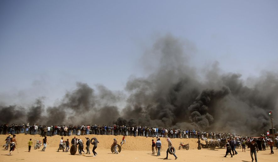 Palestinian protesters stand on sands hill as others carry tires to burn during clashes with Israeli troops along Gaza's border with Israel, east of Khan Younis, Gaza Strip, Friday, April 6, 2018. Palestinians torched piles of tires near Gaza's border with Israel on Friday, sending huge plumes of black smoke into the air and drawing Israeli fire that killed one man in the second large protest in the volatile area in a week. (AP Photo/Adel Hana)